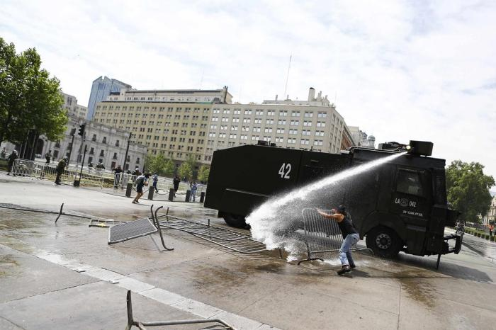 A Mapuche Indian activist throws a barrier to a riot police vehicle during a protest against Columbus Day in Santiago October 12, 2014. This year marks the 522th anniversary of Christopher Columbus' arrival to the Americas. Many indigenous people in Latin America consider it the day Columbus brought slavery, disease, colonisation and genocide from Europe to the Americas. REUTERS/Ivan Alvarado