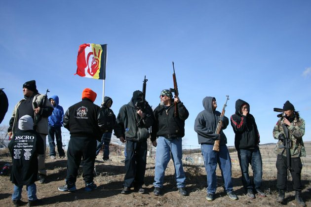 Remembrance: Members of the American Indian Movement stand near the Wounded Knee Massacre Monument