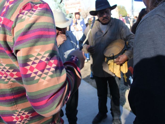 Tribal members form a small circle and play an Apache song while others dance around them outside the San Carlos Apache tribal administrative offices. (Photo: Carina Dominguez, Cronkite News Service)